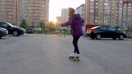 paten yapma : Slow motion girl skateboarding on city street while evening sunset. Teenager girl riding skateboard on sunny street in cityscape background. Youth lifestyle. Extreme sport