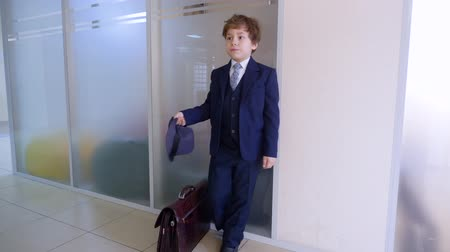 имитация : School boy in business suit and hat standing in school corridor before class. Serious businessman waiting in hall inside business office. Business children portrait Стоковые видеозаписи