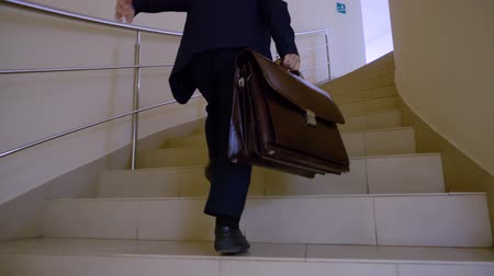 aktatáska : Schoolboy with briefcase running up by stairs to lesson in school corridor. Young business man quickly walking upstairs in hall business office Stock mozgókép