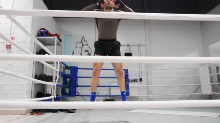 kaslar : Male fighter jumping while warm up training on boxing ring. Boxer man doing jump exercise in fight club. Sport training. Healthy lifestyle Stok Video