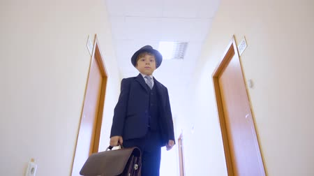 hala : Young boy in business suit, hat standing in school corridor and looking to camera. Low angle view young businessman with briefcase in business office hall looking down to camera