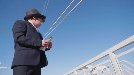 emit : Carefree young boy throwing money cash from bridge low angle view. Young boy looks like businessman waste money on pedestrian bridge. Spending money concept slow motion Stock Footage