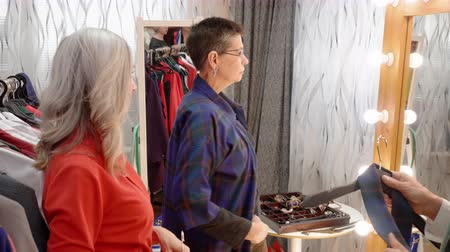 выбирать : Mature woman trying clothes front mirror in clothing shop. Adult woman choosing new clothes together friends in boutique. Female shopping. Season sale concept Стоковые видеозаписи