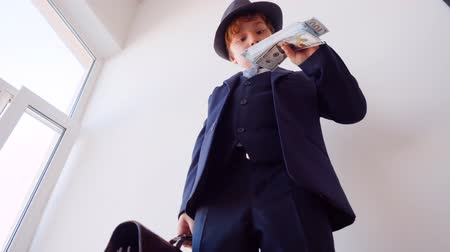 utánzás : Earning money in business. Boy businessman sniffes cash dollars and looks at huge pack of banknotes in his hand, low angle view. Stock mozgókép