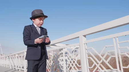 schooler : Little boy looks like a businessman in suit and hat is wasting money. He throws cash dollars banknotes in the air from the bridge on the street. Freedom from money concept.