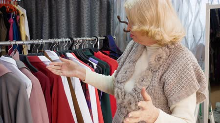 emeryt : Elderly blonde woman is choosing clothes in clothing shop. She takes clothes off the rack and looks at them talking with seller. Shopping concept.