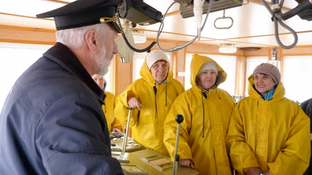 cabins : Elderly grey-haired captain of the Norway ship in the wheelhouse is talking with his team of sailors and workers in yellow raincoats. He gives them instructions before trip. Stock Footage