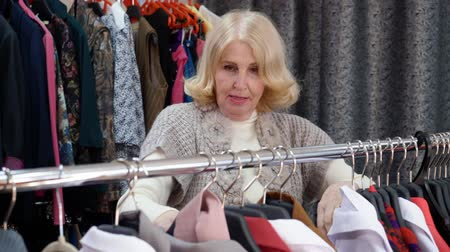 falar : Elderly blonde woman in is choosing clothes in clothing shop. She takes clothes off the rack and looks at them. Shopping concept.