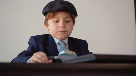 имитация : Boss is looking at money and document through the magnifier. Child boy looks like entrepreneur, works in his office sitting at the table. Boy in formal wear with cap Стоковые видеозаписи