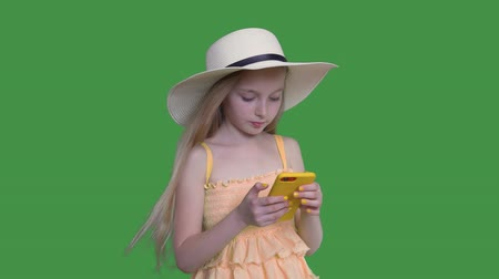 tenso : Blonde pre-teen child girl with long windy hairs in summer hat and yellow dress. She is browsing mobile phone on green screen background and touching a screen, keyed alpha channel.