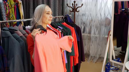 choise : Senior woman at shopping in fashion boutique. She is choosing elegant pink dress in store. Buyer is holding hanger with dress in her hands.