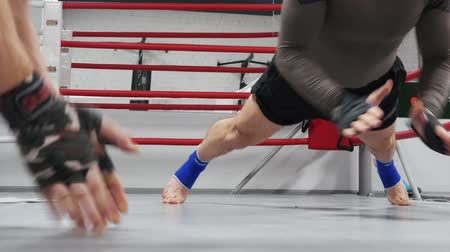 boksör : Two men fighters on professional intensive training in gym. They make push ups with claps on the floor on ringside during workout in fight club.