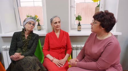 socializing : Senior three women sit and discuss their problems on friend meeting. They are in pesioners club. Wearing in elegant dresses. Stock Footage