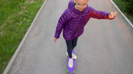 schoolkid : Pre-teen girl in purple jacket is riding on purple skateboard in city park. She is skating on asphalt, overhead view. Outdoor activities concept. Stock Footage