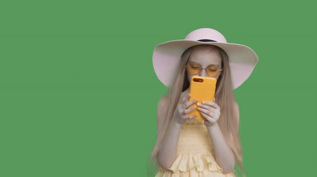 pré adolescente : Blonde pre-teen child girl with long hairs in summer hat, sunglasses and yellow dress. She is reading smartphone on green screen background and touching a screen, keyed green screen alpha channel