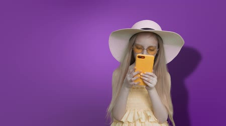 tenso : Blonde pre-teen child girl with long windy hairs in summer hat, sunglasses and yellow dress. She is reading smartphone on purple wall background and touching a screen, keyed purple screen.