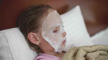 dermatologia : Portrait of child girl with cloth mask on the face, side view. Skin care procedure at home for teen problem skin. Moisturizing face mask fo kid.