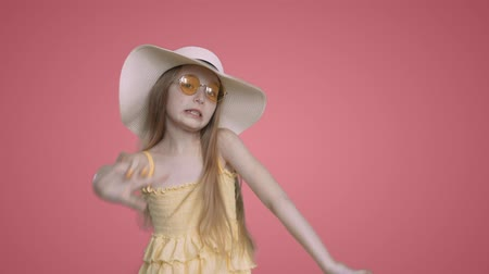 tancerze : Summer pretty girl with long hairs in yellow sunglasses. Child girl in yellow dress and hat is dancing and singing on pink background. Happy teen on vacations. Wideo