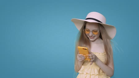 závislost : Smiling child girl in yellow summer dress, sunglasses and hat is browsing smartphone on blue wall background. Pretty girl with blonde long hairs and cute face.