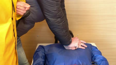 paramedics : First aid courses for people. Man learns to make compression heart massage on mannequin in the presence of an instructor, hands closeup.