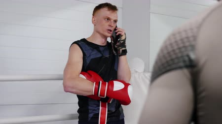 discutir : Sportsman is talking mobile phone on ringside. He is having a training in fight club. Serious professional fighter calling on smartphone to discuss his problems.