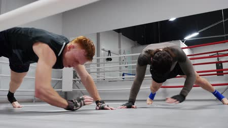 pozisyon : Workout of two professional fighters. Fighters are training on ringside make exercises in plank synchronously and simultaneously in fight club. Stok Video