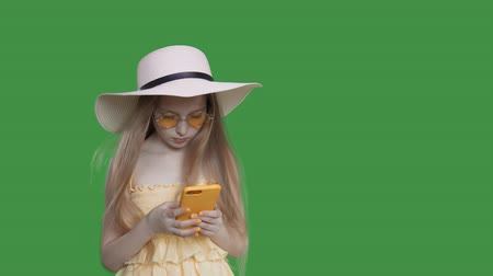 czytanie : Pre-teen child girl with long hairs is browsing phone on summer vacations. She is in beach style wearing yellow dress, sunglasses and hat, yellow smartphone and manicure. Green screen Alpha channel
