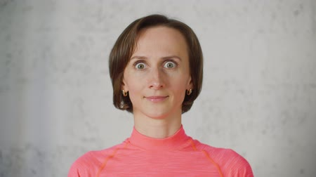 актер : Portrait of young woman in pink turtleneck opens and closes her eyes portraying an emotion of surprise. Big eyes and smiling face on video portrait.