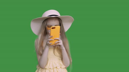 tenso : Child girl is browsing he smartphone and surfing ib social media. She is wearing yellow dress, hat and sunglasses. She covers her face with the phone. Keyed green screen alpha channel