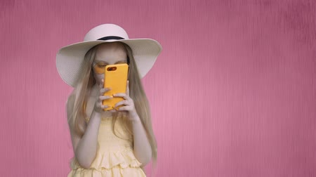 czytanie : Girl holds her smartphone at person. She is looking something surfing in internet. Pre-teen child gisr is wearing in yellow clothes: dressand hat. She is with yellow phone and manicure. Wideo
