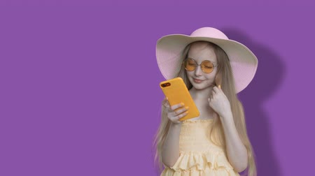 neutro : Little Smart Caucasian Girl Browse Mobile Phone. Glamour Blonde in Glasses and Straw Hat with Smartphone. Wind Blowing Long Hair. Modern Electronic Gadget Addict Child on Solid Colorful Background