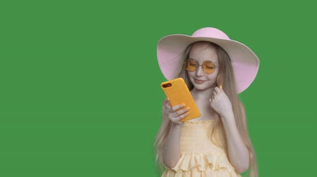 alfa : Little Fancy Caucasian Girl Surfing Mobile Phone. Glamour Blonde in Glasses and Straw Hat Hold Smartphone. Wind Blowing Long Hair. Comunication Childhood. Alpha Channel Keyed Green Screen