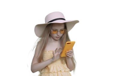 sombrero de paja : Fansy Addicted Caucasian Girl Browse Mobile Phone. Little Kid Model Wearing Glasses and Straw Hat Holding Cellphone. Wind Blowing Long Blond Hair. Fashion Child on White Solid Background Archivo de Video