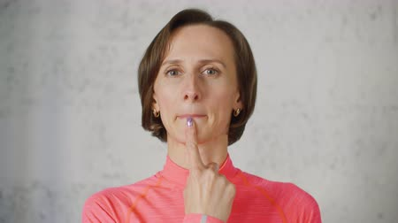 немой : Woman touch lips by finger. Sign language for people with disabilities. Portrait of woman on light background with finger on her chin under the lips meaning T-letter. She is showing sign by gesture. Стоковые видеозаписи