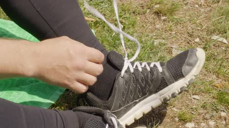 destruição : Male hands undoing shoelaces on sneakers while outdoor rest. Man unties laces on sneakers sitting on meadow grass