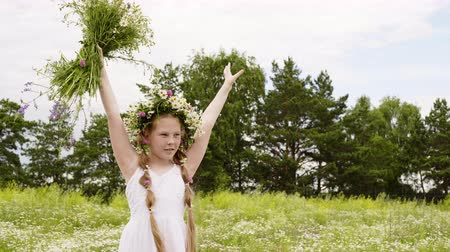 gramado : Teenager girl in flower wreath raised up hands with meadow flowers on green field. Happy girl holding in hands over head forest flowers bouquet on green lawn Stock Footage