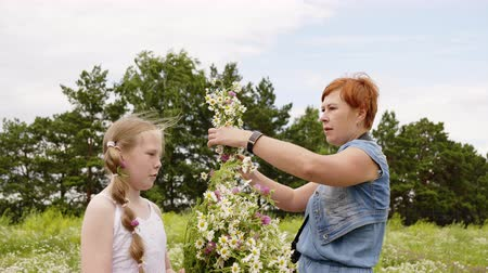 koszorú : Mom and daughter with wreath and flowers bouquet on green summer field. Mother preparing daughter to photographing with meadow flowers on lawn Stock mozgókép