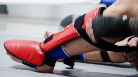 combativo : Close up athlete boxer man fighter in sportswear tying bandage shield on legs before boxing. Fighter wearing red leg shield. Kickboxer man preparing for boxing practice at gym.