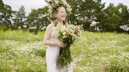 kamilla : Happy laughing child girl in white summer dress is walking on glade. She is with bouquet and wreath of daisies on flower meadow. Teen girl with long hairs and freckles on her face.