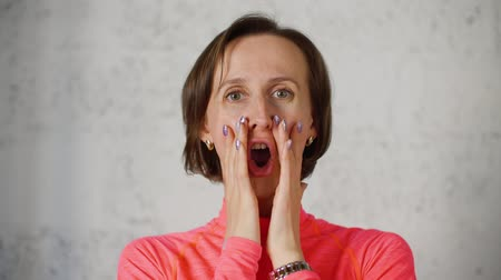 masaż twarzy : Portrait of screaming woman with hands near mouth, she makes facial gymnastics. Woman pretends she is shouting making round lips. Face on light background.