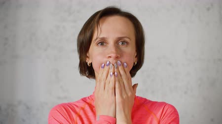 front cover : Woman does facial gymnastics exercises, puffs up her cheeks and clamps her lips with hands. Portrait of young woman covering her mouth with her hands. Wellness facial yoga against wrinkles.