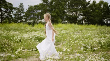 braid hairs : Young girl teenager with hair braid jumping on green meadow at summer. Romantic teenager girl in white dress rotating on green field at summer vacation