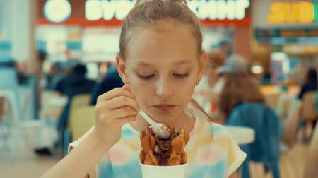 oplatka : Cute teenager girl eating ice cream in food court. Young girl teenager enjoying ice cream dessert in shopping mall cafe. Fast food and dessert food concept