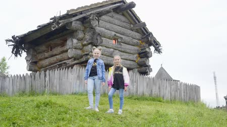 hag : Two girl teenager standing on green lawn on rotating fairy tale hag house. Teenager girl posing on wooden house old witch in fairy tale village. Wooden house fairy grandmother Yaga