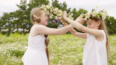 kamilla : Two girl wearing floral wreath having fun on blooming meadow at summer day. Happy girl teenager playing with flower wreath on summer field in countryside