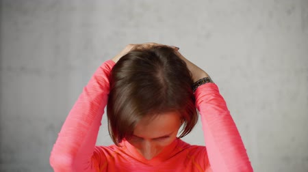 nape : Wellness exercise for cervical osteochondrosis. Woman puts hands on back of her head and tilts her head forward stretching neck muscles. Portrait of young woman on light background.
