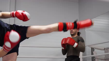 açıklayan : Personal training for youg professional kickboxer in fight club. Kickboxing trainer shows and explain sportsman leg blow technic kicks on ring in gym. Sport people workout concept.