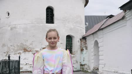 памятники : Child girl on a tour of the ancient fortress. Teen girl in jacket walks to camera on ancient white wall background. She is posing on camera. Young tourist in landmark.