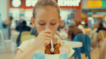 gofret : Sad teenager girl eating chocolate ice cream in cafe. Young girl teenager eating ice cream dessert with waffle in gelato cafe. Fast food and dessert food concept Stok Video