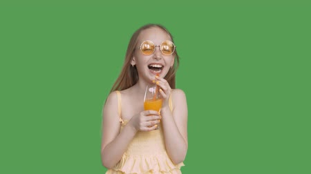 антиоксидант : Laughing girl holding in hands orange juice glass on transparent background. Happy girl teenager in yellow glasses with orange cocktail on chroma key background. Alpha channel, keyed green screen. Стоковые видеозаписи